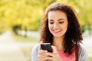 Student Text Messaging On Smart Phone At Campus
