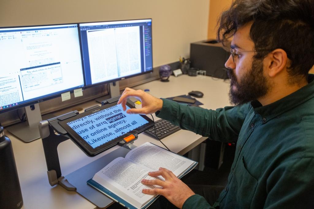 Associate Director, Amrou Ibrahim, using an electronic magnifier.